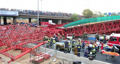 Paramedics and firefighters work to extricate a passenger from a taxi after a scaffolding bridge collapsed on the M1 next to the Grayston Drive off-ramp in Sandton on October 14, 2015. Picture: Neil McCartney/The Citizen