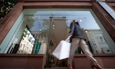 A customer exits the Chloe boutique, operated by Cie. Financiere Richemont SA, on Sloane Street, in London.  Image: Jason Alden/Bloomberg