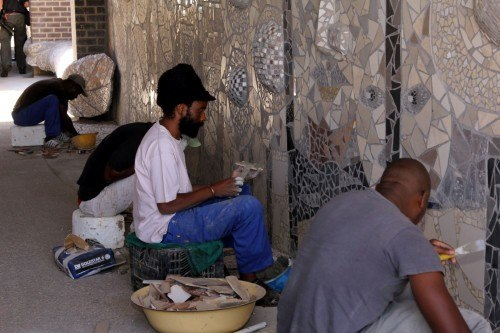 Residents from surrounding informal settlements create art work at a Steyn City underpass.