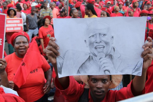 A man holds up a drawing of Julius Malema.