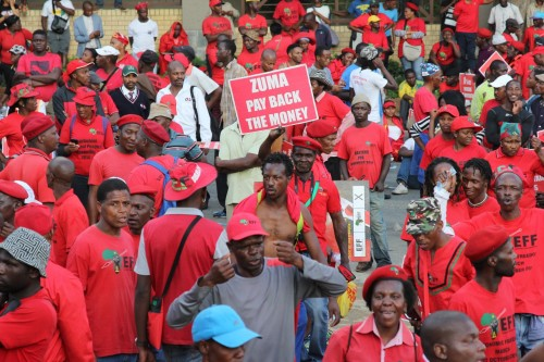 EFF members hold placards during the march to the JSE.