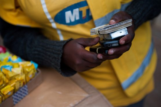 A vendor holds mobile phones and airtime scratch cards at a Mobile Money stall operated by MTN Group on a street in Kigali, Rwanda. Image: Will Boase/Bloomberg