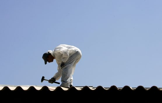 A worker removes asbestos from the roof of a house. Image: Jerry Lampen, Reuters