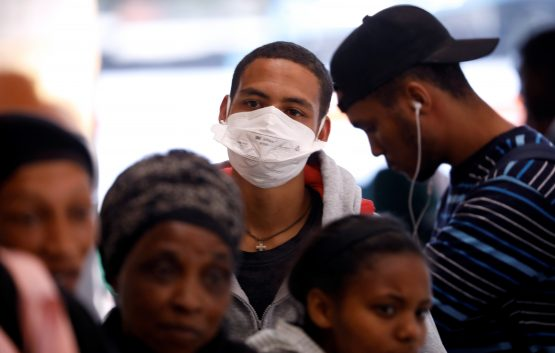 A commuter wears a mask to combat the spread of Covid-19 at a bus depot in Cape Town. Image: Reuters, Mike Hutchings