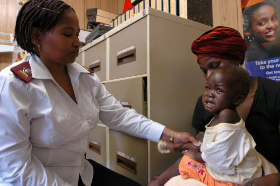 Nurse Zonke Dlalisa applies medicine to the skin of a child who has lesions caused by Aids at an HIV/Aids clinic in the rural Emmaus Hospital in KwaZulu-Natal. Image: Naashon Zalk/Bloomberg News.