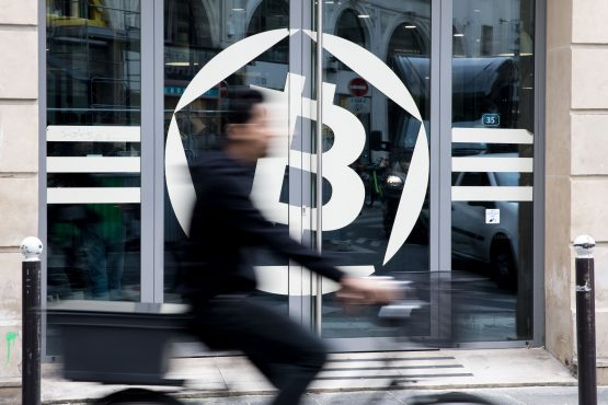 A cyclist passes the entrance to the La Maison du Bitcoin bank in Paris. Picture: Christophe Morin/Bloomberg