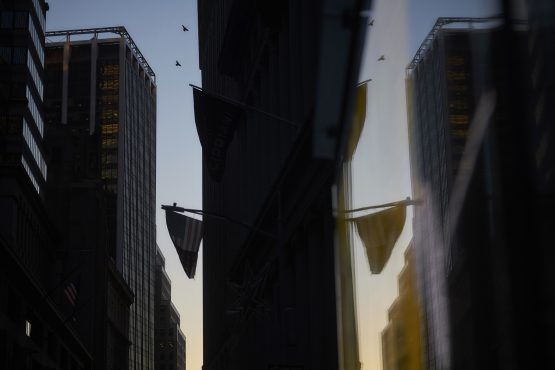 The sun rises on Wall Street near The New York Stock Exchange. Image: John Taggart/Bloomberg