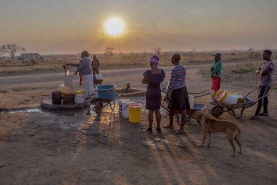 People stood in line at the borehole waiting for their turn to use the hand pump to fill their containers with water. Image: Cynthia R Matonhodze, Bloomberg