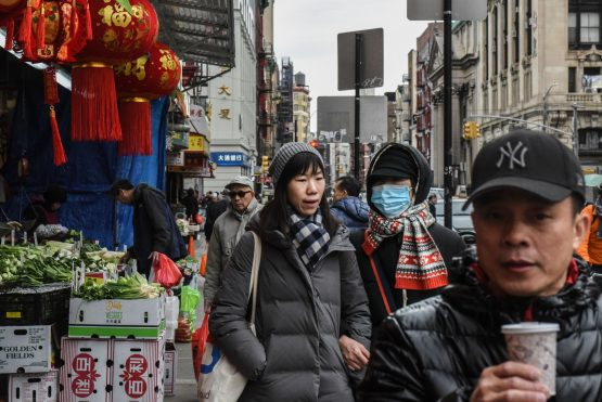 A pedestrian wearing face mask walks along a street in the Chinatown neighbourhood of New York, US. Image: Stephanie Keith/Bloomberg