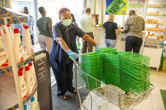 A worker wearing a protective face replenishes baskets a Dis-Chem Pharmacies store in Pretoria. Image: Waldo Swiegers/BloombergImage: Supplied