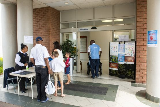 Visitors queue at a health screening desk outside the entrance to Netcare Pretoria East Hospital on Monday, March 16, 2020. Image: Waldo Swiegers/Bloomberg
