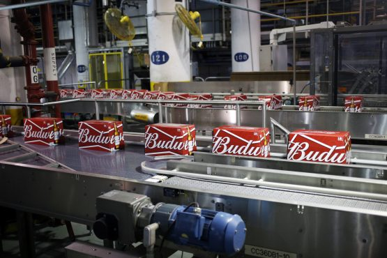 Cases of beer bottles move along conveyor belts at the Anheuser-Busch InBev Budweiser bottling facility in St Louis, Missouri, US. Picture: Luke Sharrett/Bloomberg