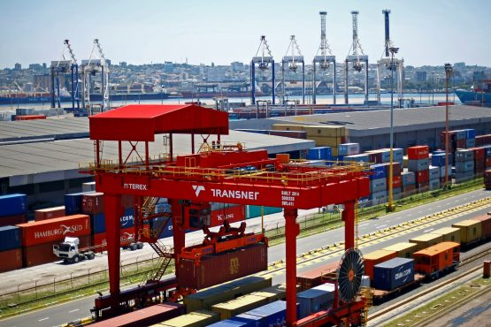 A crane operator unloads shipping containers from freight wagons at the Port of Durban, operated by Transnet. Image: Kevin Sutherland, Bloomberg