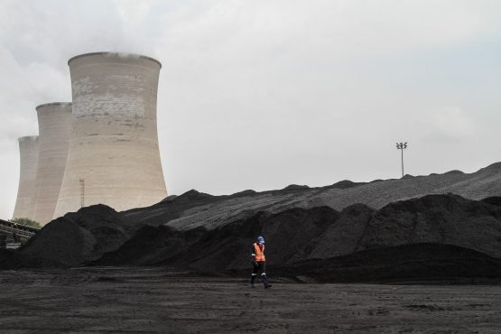 A worker walks past coal stores at the Grootvlei power station, operated by Eskom Holdings. Picture: Bloomberg