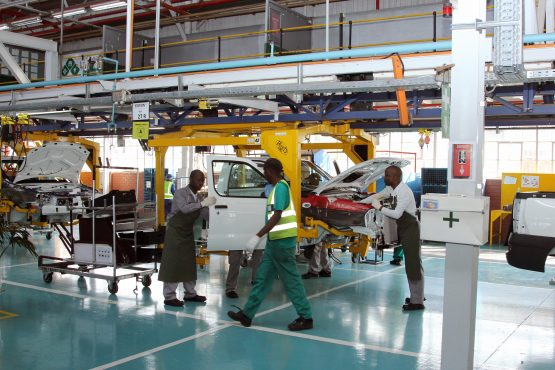 Automobile body shells hang from cradles on the assembly line at a car plant in South Africa. Image: Moneyweb