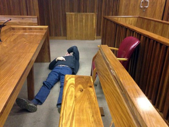 Porritt lying on his back in court in June 2017. A few hours later he was caught on CCTV walking around Milpark Hospital with ease and confidence. Picture: Moneyweb