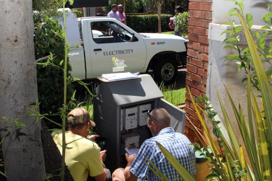 Technicians inspect the meters before removal.