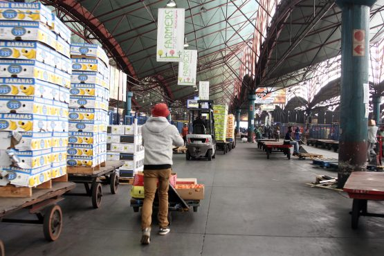 A worker pushes a trolley full of produce on the dirty trading floor of the Tshwane Fresh Produce Market. Picture: Moneyweb
