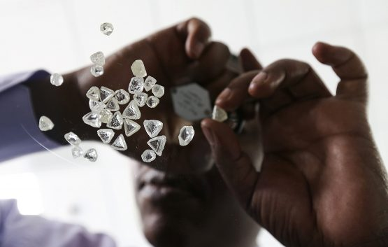 An employee inspects a pile of uncut diamonds at DTC Botswana, a unit of De Beers, in Gaborone. Picture: Chris Ratcliffe/Bloomberg