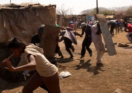 Residents  battle with police in a protest against poor service delivery in the fields of water, electricity, housing,sanitation and health in the informal settlement of Zone 1, Protea Glen,  Johannesburg, South Africa, Monday, Sept. 3, 2007. South Africans, protesting against the government's slow delivery of housing, water and electricity, attempted to block the Golden Highway near the township of Sebokeng, south of Johannesburg, setting fire to tires. Police fired rubber bullets to clear demonstrators and removed the tires from the road. Photographer: Greg Marinovich/Bloomberg News.