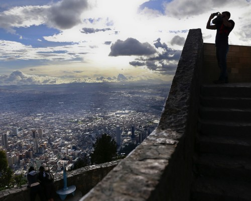 A tourist takes a photograph of the city from Cerro de Monserrate in Bogota, Colombia, on Tuesday, June 16, 2015. Colombia's fiscal deficit will widen next year to the most since 2010 amid lower crude prices, according to the government's latest financial plan. Photographer: Cassi Alexandra/Bloomberg