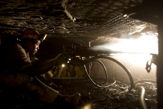 A mineworker uses a drill on the rock face as he works deep underground at the Impala Platinum mine in Rustenburg