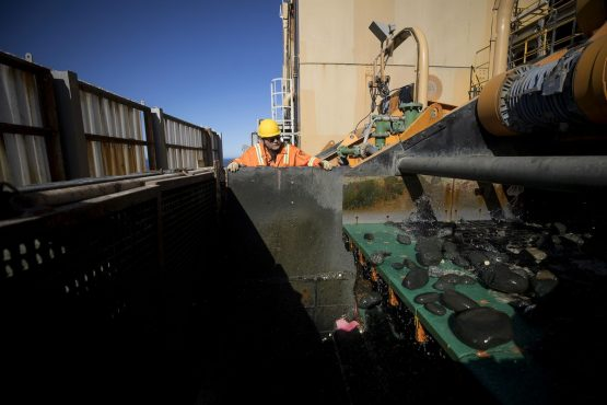 A high pressure spray cleans discarded non-diamond bearing gravel before being returned to the ocean from the Mafuta mining vessel. Picture: Simon Dawson/Bloomberg