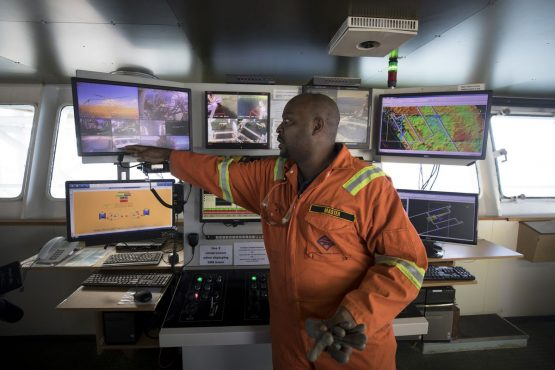 A crew member points to a digital monitors showing camera views of mooring systems in the operations room aboard the Mafuta. The vessel positions itself to scan and sample the seabed to identify the most profitable area for the ship to suck up the gems. Picture: Simon Dawson/Bloomberg