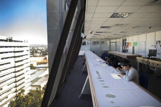 Employees grade rough diamonds using daylight to illuminate the gems at the Namibian Diamond Trading Co. processing and valuation center in Windhoek. Picture: Simon Dawson/Bloomberg
