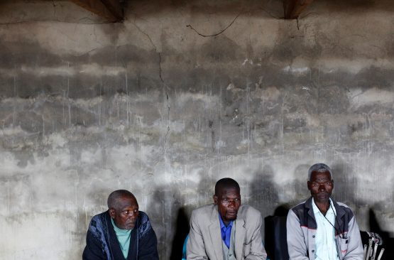 Former gold miners seen listening to speakers at a meeting for miners with silicosis in Bizana in the Eastern Cape in March 2012. Photographer: Reuters/Mike Hutchings