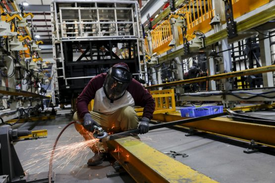 An employee operates a grinder while working on the frame of an electric vehicle. Picture: Patrick T. Fallon/Bloomberg