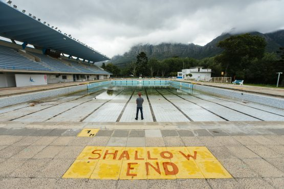 A person stands in the pool to demonstrate the severely low water level at the Newlands municipal swimming pool in Cape Town. Picture: Waldo Swiegers/Bloomberg