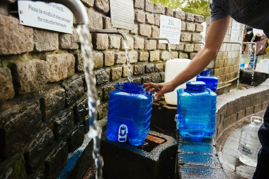Residents fill water bottles and containers at the Newlands natural water spring in Cape Town. Picture: Bloomberg