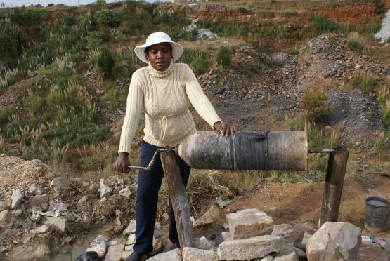 Constance, a trained nurse from Zimbabwe, operates one of the rotating drums, hoping to extract a few grams of gold, as her only means to survive. Picture: Author