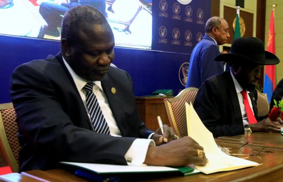 Machar (left) and South Sudan President Salva Kiir seen signing a cease fire and power sharing agreement in August 2018. Image: Mohamed Nureldin Abdallah/Reuters