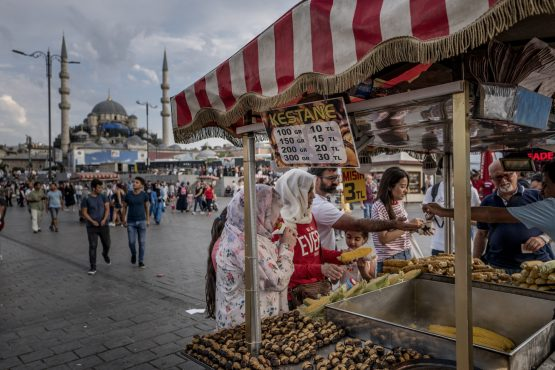 Customers purchase snacks from a mobile stall on Eminonu Square in Istanbul, Turkey, on August 17, 2018. Picture: Ismail Ferdous/Bloomberg