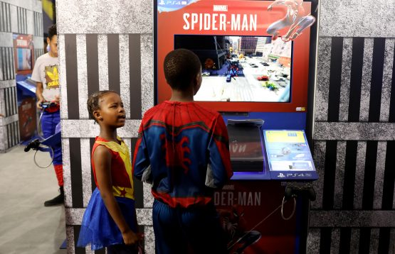 Masego Sehume reacts as his brother Botlhale plays a PS4 game during the international Comic Con at Kyalami race course. Picture: Siphiwe Sibeko/Reuters