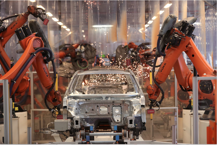 In a world of robots, carmakers are hiring more humans