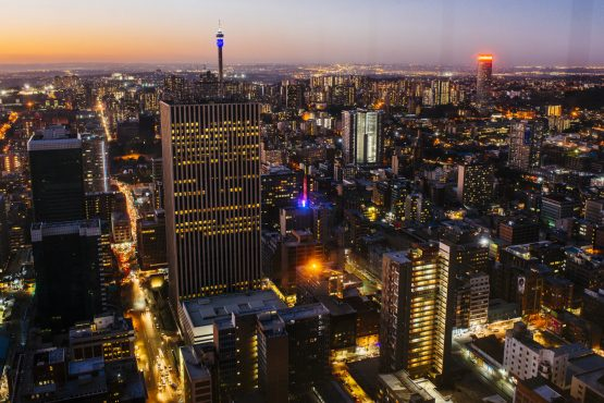 Commercial buildings and office property stand on the city skyline as night falls, as seen from the 50th floor of the Carlton Centre, in Johannesburg. Image: Waldo Swiegers/Bloomberg