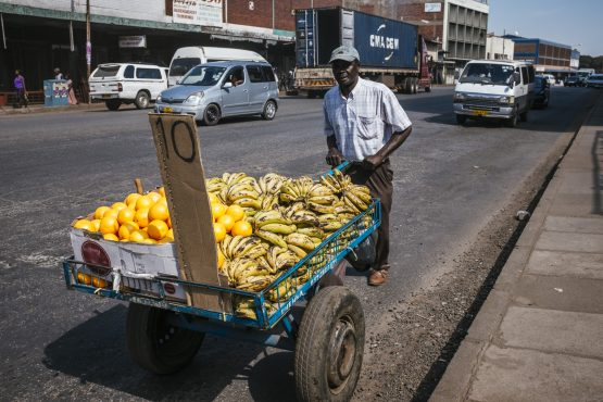 A street vendor wheels a cart containing fresh fruit produce for sale in Harare, Zimbabwe. Picture: Waldo Swiegers/Bloomberg