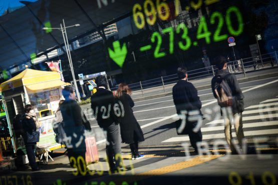 Pedestrians are reflected in an electronic stock board outside a securities firm in Tokyo, Japan. Picture: Noriko Hayashi/Bloomberg