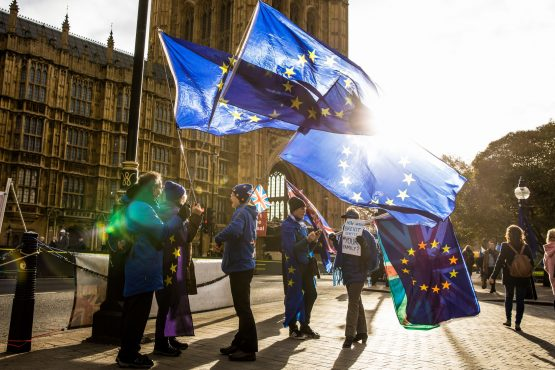 Anti-Brexit demonstrators wave EU flags outside the Houses of Parliament in London. Picture: Jason Alden/Bloomberg