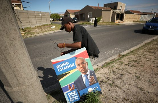 A worker prepares to attach an election poster of Mmusi Maimane's opposition DA party to a lamppost in Mitchell's Plain township in Cape Town. Picture: Reuters