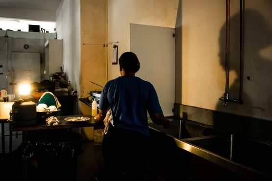 Workers in a cafe use an emergency gas-powered lamp to illuminate the kitchen after a load-shedding power outage stopped their electricity supply in Joburg. Picture: Waldo Swiegers/Bloomberg