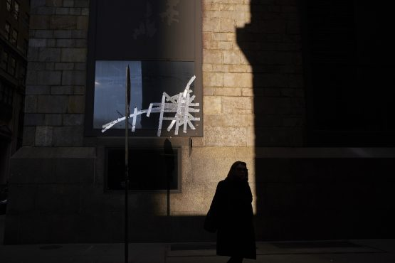 Symbolic … a pedestrian walks past a broken window near Wall Street in New York as chances of a near-term resolution in the US-China trade war have dimmed. Photographer: John Taggart/Bloomberg