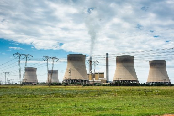 Emissions rise from a chimney stood between cooling towers at the Eskom 