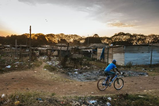 A cyclist rides along a dirt track past shanty dwellings in the Mbare township in Harare, Zimbabwe. Picture: Waldo Swiegers/Bloomberg