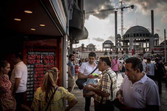People wait to change money at a currency exchange office in front of the under-construction, Taksim Square Mosque in Istanbul, Turkey. Picture: Chris McGrath/Getty Images Europe