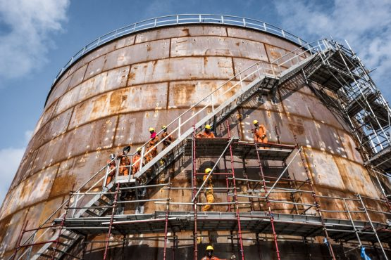 Workers climb scaffolding surrounding a storage tank at the under-construction Dangote Industries oil refinery outside of Lagos, Nigeria. Image: Tom Saater/Bloomberg