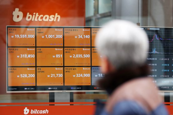 A pedestrian looks at a monitor showing the prices of virtual currencies at the Bithumb exchange office in Seoul. Picture: SeongJoon Cho/Bloomberg